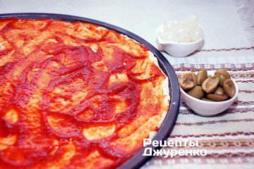 Смазать тесто томатым соусом.