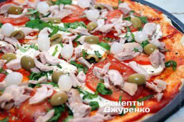 Разложить на пиццу маринованный лук и оливки.