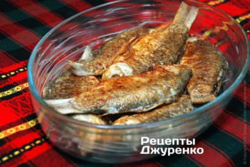 В форму, смазанную сливочным маслом, выложить обжаренных карасей.
